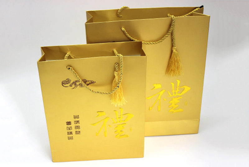 golden colored plain paper bags with handles